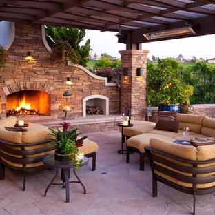 Patio - mid-sized mediterranean backyard stone patio idea in Los Angeles with a fire pit and a pergola