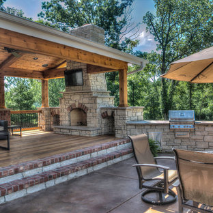 Large elegant backyard stamped concrete patio photo in St Louis with a fire pit and a roof extension