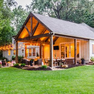 Immagine di un patio o portico stile rurale di medie dimensioni e dietro casa con cemento stampato e un tetto a sbalzo