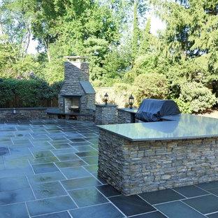 Immagine di un grande patio o portico classico dietro casa con pavimentazioni in pietra naturale e nessuna copertura