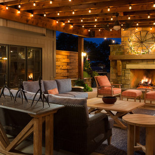 Design ideas for a large rustic back patio in Kansas City with concrete slabs, an awning and a fireplace.