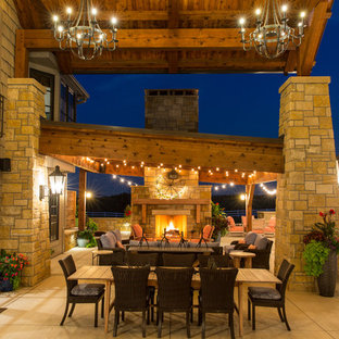 Large rustic back patio in Kansas City with a fire feature, concrete slabs and an awning.