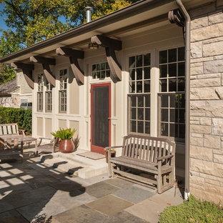 Immagine di un patio o portico country di medie dimensioni e dietro casa con un focolare, pavimentazioni in pietra naturale e una pergola