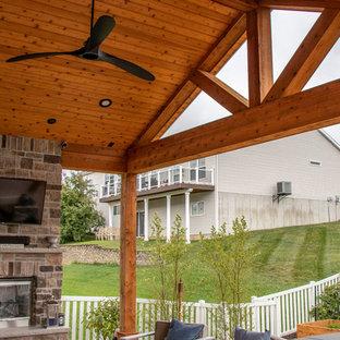 Immagine di un patio o portico di medie dimensioni e dietro casa con un caminetto, cemento stampato e un tetto a sbalzo