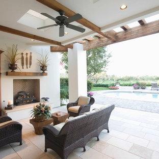 Foto di un patio o portico mediterraneo di medie dimensioni e dietro casa con un caminetto, piastrelle e un tetto a sbalzo
