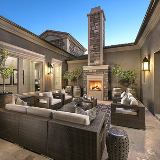 Inspiration for a large transitional courtyard stone patio remodel in Phoenix with no cover and a fireplace