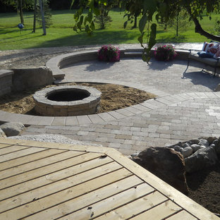 Large mountain style backyard concrete paver patio photo in Detroit with a fire pit and a gazebo
