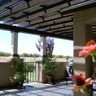 Example of a large tuscan backyard concrete patio design in Other with a roof extension