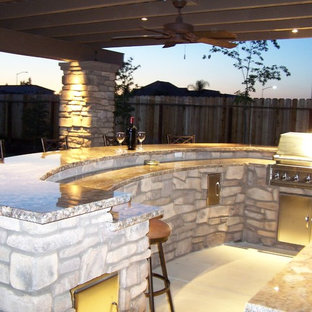 Inspiration for a mid-sized craftsman backyard concrete patio kitchen remodel in Other with a pergola