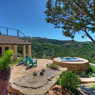 Idee per un ampio patio o portico boho chic dietro casa con pavimentazioni in pietra naturale