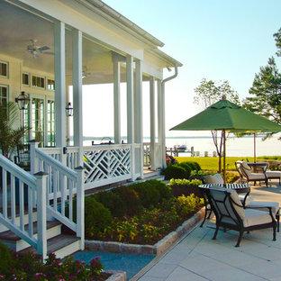 Esempio di un grande patio o portico tropicale davanti casa con pedane e un tetto a sbalzo