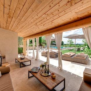 Exemple d'une grande terrasse arrière tendance avec une extension de toiture.
