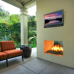 Ispirazione per un piccolo patio o portico tropicale dietro casa con un focolare, un tetto a sbalzo e lastre di cemento