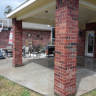 Example of a mid-sized arts and crafts backyard concrete patio kitchen design in Houston with a roof extension