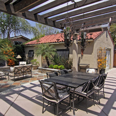 Tuscan patio photo in Orange County with a fire pit and a pergola