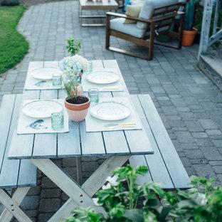 Foto di un ampio patio o portico stile marinaro dietro casa con cemento stampato e nessuna copertura