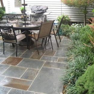 Foto di un patio o portico classico di medie dimensioni e dietro casa con piastrelle e nessuna copertura