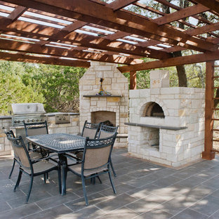 Inspiration for a huge southwestern backyard tile patio kitchen remodel in Austin with a pergola