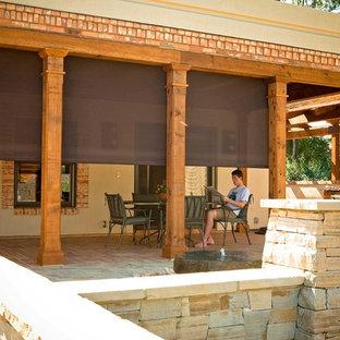 Ispirazione per un patio o portico mediterraneo di medie dimensioni e dietro casa con pavimentazioni in mattoni e un tetto a sbalzo