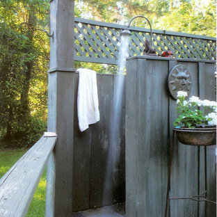 Example of an island style outdoor patio shower design in New Orleans with decking and no cover