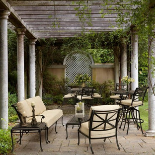 Inspiration for a mid-sized timeless courtyard brick patio remodel in DC Metro with a pergola