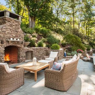 Esempio di un ampio patio o portico classico dietro casa con un focolare e nessuna copertura