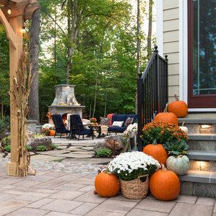 Ispirazione per un grande patio o portico stile rurale dietro casa con un caminetto, pavimentazioni in cemento e una pergola