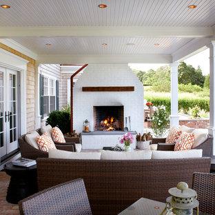 Immagine di un patio o portico costiero di medie dimensioni e dietro casa con un focolare, pavimentazioni in mattoni e un tetto a sbalzo