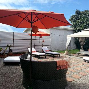 Esempio di un grande patio o portico tropicale dietro casa con ghiaia