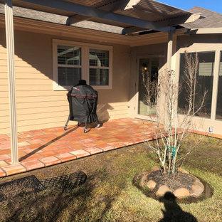 Foto di un patio o portico american style dietro casa con piastrelle e una pergola