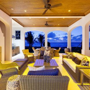 Esempio di un grande patio o portico dietro casa con un caminetto, piastrelle e un gazebo o capanno