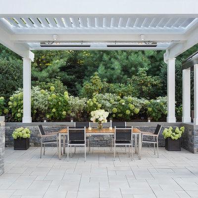 Transitional backyard concrete paver patio container garden photo in Boston with a pergola