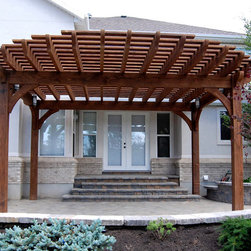 Evans Oversize Pergola Front Entrance Makeover - New durable 18x20 timber frame arbor pergola kit with lighting is installed over the front entryway within a few hours. The roof is designed with an extended overhang for added shade. The steps were extended out in brick and the patio as well.