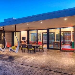 Idée de décoration pour une terrasse arrière design de taille moyenne avec une dalle de béton et une extension de toiture.