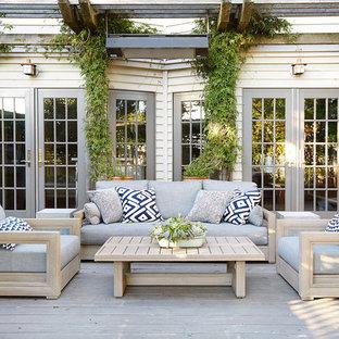 Réalisation d'une terrasse arrière tradition de taille moyenne avec une pergola.