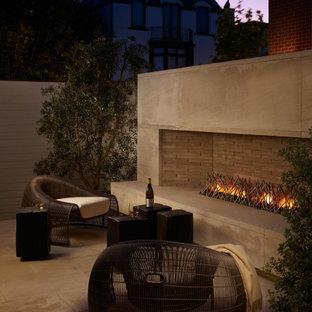 Idee per un grande patio o portico contemporaneo dietro casa con piastrelle, nessuna copertura e un caminetto