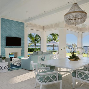 Example of a large beach style backyard tile patio kitchen design in Miami with a roof extension
