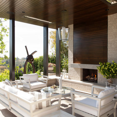 Example of a trendy patio design in Los Angeles with a roof extension and a fireplace