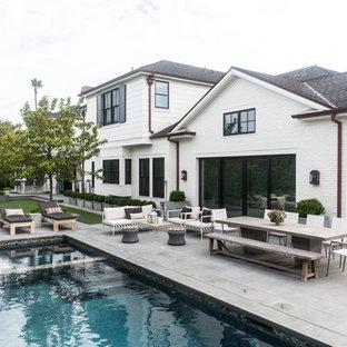 Idee per un ampio patio o portico tradizionale dietro casa con lastre di cemento e nessuna copertura