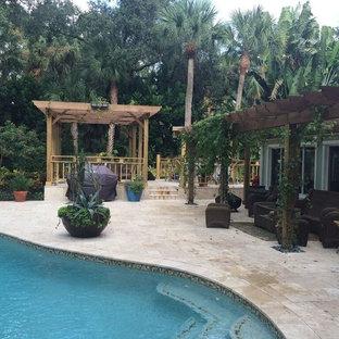Ispirazione per un patio o portico tropicale dietro casa con pavimentazioni in pietra naturale e una pergola