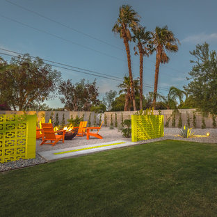 Example of a large midcentury modern backyard gravel patio design with a fire pit