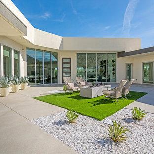 Idee per un patio o portico minimalista con un focolare, lastre di cemento e nessuna copertura