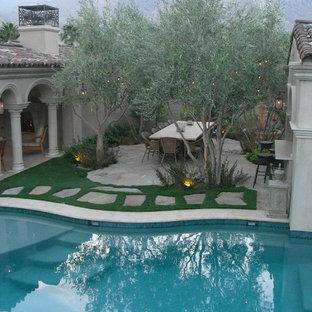 Foto di un ampio patio o portico mediterraneo in cortile con un focolare e una pergola