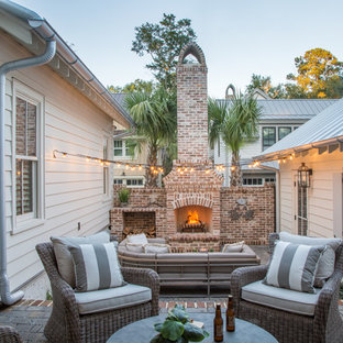 Country courtyard brick patio photo in Atlanta with no cover and a fireplace