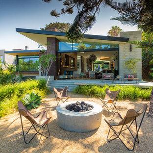 Idee per un patio o portico moderno dietro casa con un focolare, ghiaia e nessuna copertura