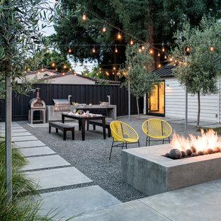Cette photo montre une terrasse et balcon arrière tendance avec un foyer extérieur et du gravier.