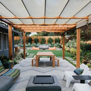 Modelo de patio contemporáneo, de tamaño medio, en patio trasero, con adoquines de hormigón y pérgola