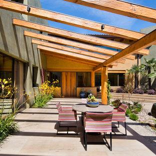 Immagine di un grande patio o portico stile americano dietro casa con fontane, una pergola e piastrelle