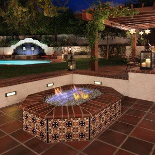 Foto di un grande patio o portico mediterraneo dietro casa con un focolare, piastrelle e una pergola
