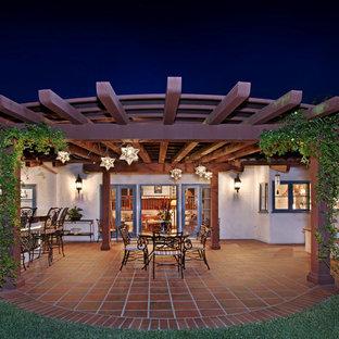 Esempio di un grande patio o portico mediterraneo dietro casa con piastrelle e una pergola